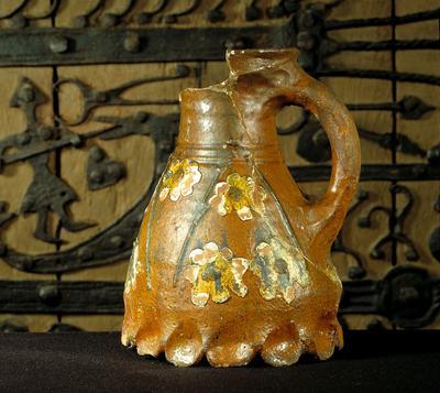 Kande af glaseret, rødbrændt lertøj fundet i Skt. Hans kilde i Roskilde, hvor den må være tabt af pilgrimme, der ville drikke af kildens hellige vand. Kanderne med den pålagte, flerfarvede dekoration er lavet i Østdanmark. Datering: o. 1300 (foto: Ukendt)
